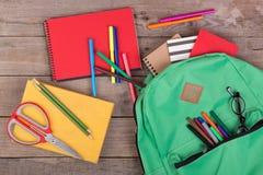 Rucksack und Schulbedarf: Bücher, Bleistifte, Notizblock, Filzstifte, Brillen, Scheren auf braunem Holztisch Stockfotografie