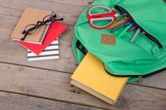 Rucksack und Schulbedarf: Bücher, Bleistifte, Notizblock, Filzstifte, Brillen, Scheren auf braunem Holztisch Lizenzfreie Stockfotografie