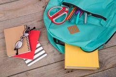 Rucksack und Schulbedarf: Bücher, Bleistifte, Notizblock, Filzstifte, Brillen, Scheren auf Holztisch lizenzfreie stockbilder