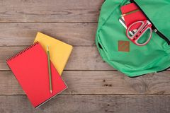 Rucksack- und Schulbedarfbücher, Bleistifte, Notizblock, Scheren auf braunem Holztisch Stockbilder