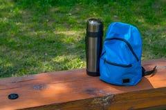 Rucksack und Thermosflasche für das Kampieren auf einer Holzbank stockbild