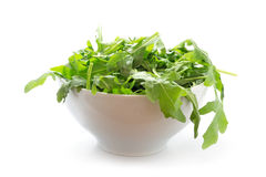 Rucola or arugula, fresh green rocket salad  in a white bowl, is Stock Images
