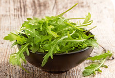 Rucola in black bowl. On old wooden table Royalty Free Stock Photo