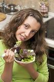 Rucola de la consumición de la muchacha y ensalada del mangel Fotos de archivo