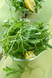 Rucola in glass bowl on green napkin stock photo