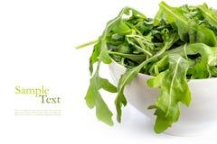 Rucola ou arugula, salade de fusée fraîche dans une cuvette en céramique blanche, Image stock