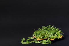 Rucola salad in orange plate. Fresh and green rucola salad in orange plate. Plate is in shape of autumn maple leaf. Some leaves are dropped out of plate. The Royalty Free Stock Image