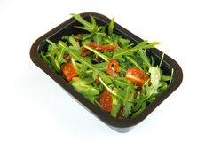 Rucola salad with tomatoes. Salad with arugula, fresh and dried tomatoes and dried plums in a take-out package on a white background Stock Images