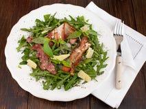 Rucola sallad med grillad bacon och parmesan Arkivbild