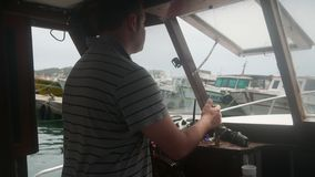 Rudder, fishing boat. Man driving a fishing ship in the port stock video footage