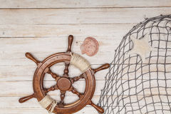 Rudder of sailing ship, fishing net with sea shells on wooden background Stock Image