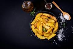 Ruddy Baked-aardappelwiggen met rozemarijn en knoflook Royalty-vrije Stock Foto's