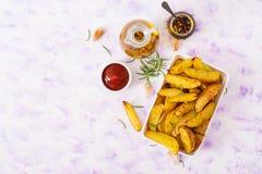 Ruddy Baked-aardappelwiggen met rozemarijn en knoflook Royalty-vrije Stock Foto