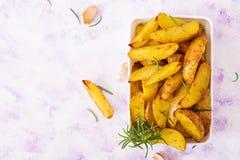 Ruddy Baked-aardappelwiggen met rozemarijn en knoflook Stock Foto