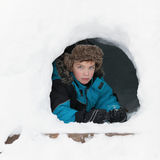 Ruddy beautiful boy in winter clothes peeking out of snow mountain, Royalty Free Stock Images