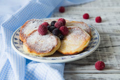 Ruddy cheesecakes with powdered sugar and berries. Stock Image