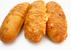 The ruddy long loaf of bread. Is strewed by cheese isolated on a white background Stock Photos