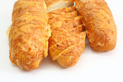 The ruddy long loaf of bread. Is strewed by cheese isolated on a white background Stock Images