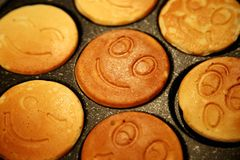 The ruddy pancakes with smiles on the pan Royalty Free Stock Photography