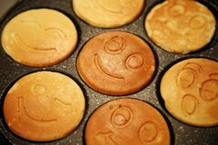 The ruddy pancakes with smiles on the pan Stock Images