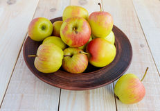 Ruddy ripe green apples in a brown bowl Stock Photo