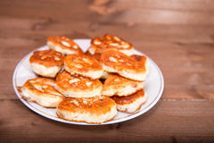 Ruddy small pancakes on a wooden table Stock Photos