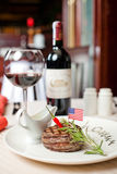 Ruddy steak and red wine. Well done steak and red wine with spicy chilli sauce on the table Royalty Free Stock Photos