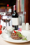 Ruddy steak and red wine. Well done steak and red wine with spicy chilli sauce on the table Stock Image