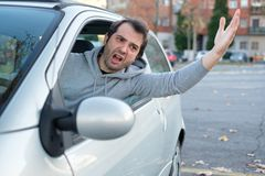 Rude and aggressive driver stressed in the traffic jam. Closeup portrait of aggressive male driver honking in traffic jam Royalty Free Stock Photography