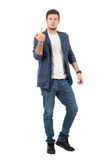 Rude attitude young aggressive man showing middle finger gesture at camera. Full body length portrait isolated over white background Stock Photography