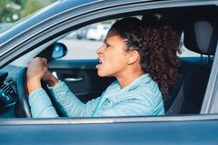 Rude black woman driver arguing and driving car. Aggressive woman driving car shouting at someone stock photos