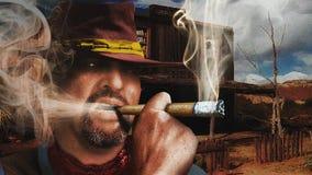 Rude cowboy smoking tobbaco. At west far Royalty Free Stock Photography