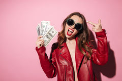Rude crazy girl in leather jacket holding money banknotes. Portrait of an arrogant crazy girl in leather jacket holding money banknotes and showing middle finger Stock Photography