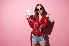 Rude crazy girl in leather jacket holding money banknotes. Portrait of a rude crazy girl in leather jacket holding money banknotes and showing middle finger Royalty Free Stock Photography