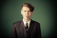 Rude handsome young teenage boy. With an attitude problem sticking out his tongue at the camera with a fierce expression royalty free stock photo