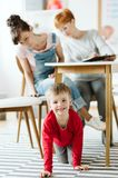 Rude kid sitting under the table during therapy for ADHD with his mother and professional therapist stock photography