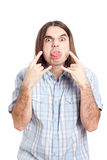 Rude man gesturing and sticking out tongue. Young long haired rude man gesturing and sticking out tongue, isolated on white background Royalty Free Stock Photo