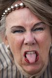 Rude old woman. Closeup of rude old woman sticking out her tongue Royalty Free Stock Photos