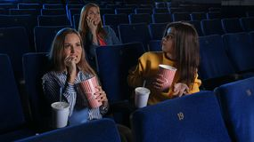 Rude woman talking on phone and disturbing other viewers. Rude women talking on phone and disturbing other viewers in cinema stock images