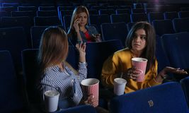 Rude woman talking on phone and disturbing other viewers. Rude women talking on phone and disturbing other viewers in cinema stock image
