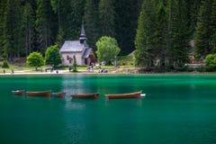 Ruderboote am Braies See mit einer Kirche im Hintergrund lizenzfreie stockfotos