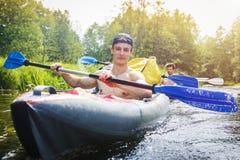 Ruderer in einem Kajak mit Rudern segeln entlang den Fluss an einem hellen Sommertag Junge athletische Männer rudern Ruder auf de stockfotografie