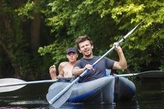 Ruderer im Boot segeln entlang Fluss- und Reihenruder am Sommertag Sportkerle flößen hinunter Fluss freizeit Gruppe Kayakers lizenzfreie stockfotografie