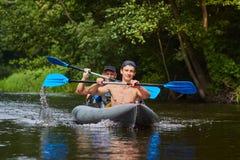 Ruderer mit Rudern in einem Kanu auf dem Flößen entlang dem Fluss an einem sonnigen Tag des Sommers Freunde schwimmen in einem Bo stockfotos