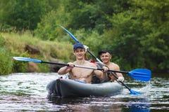 Ruderer werden entlang Fluss in einem Kajak geflößt Zwei Freunde schwimmen im Boot auf Fluss und rudern Ruder auf dem Wasser lizenzfreies stockfoto