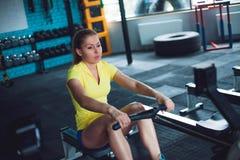 Rudern in der Turnhalle Training der jungen Frau unter Verwendung der Rudermaschine lizenzfreies stockbild