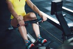 Rudern in der Turnhalle Training der jungen Frau unter Verwendung der Rudermaschine lizenzfreie stockbilder