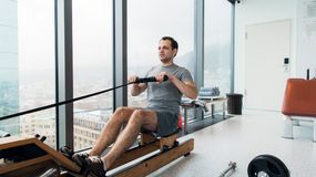Rudern mit Energie Seitenansicht des jungen Mannes in der Sportkleidung, die Rudersport vor Fenster an der Turnhalle tut lizenzfreies stockfoto