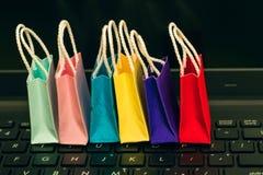Rudern Sie bunte Papiereinkaufstaschen mit Handy auf einem Laptop k stockbild