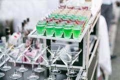 Rudern Sie Linie von verschiedenen farbigen alkoholischen Cocktails auf einer Partei Hochzeitstag oder Geburtstag stockfotos